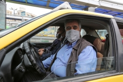 An Iranian taxi driver sits inside a transparent partition to isolate himself from passengers at Aryashahr station, a transport hub in west Tehran on April 26, 2020, as cab services have been among the hardest hit since the country's coronavirus outbreak. (Photo credit: ATTA KENARE/AFP via Getty Images)