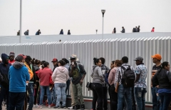 """Asylum seekers queue for a turn for an asylum appointment with US authorities, at the US-Mexico El Chaparral crossing port in Tijuana, Baja California State, Mexico, on May 31, 2019. - Washington will impose a five percent tariff on all goods from Mexico starting on June 10, a measure that will last until """"illegal migrants"""" stop coming through the country into the US, President Donald Trump said Thursday. (Photo credit should read GUILLERMO ARIAS/AFP via Getty Images)"""