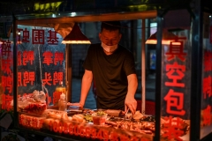 A man wearing a facemask sells food at his stall on a street in Wuhan, Chinas central Hubei province on May 20, 2020. - China has largely brought the coronavirus under control within its borders since the outbreak first emerged in the city of Wuhan late last year. (Photo by HECTOR RETAMAL/AFP via Getty Images)