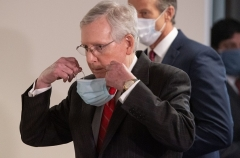 Senate Majority Leader Mitch McConnell (R-Ky.) removes his mask before speaking at a May 5 news conference. (Photo by SAUL LOEB/AFP via Getty Images)