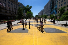 """D.C. Mayor Muriel Bowser had """"Black Lives Matter"""" painted in huge yellow letters on a street near the White House. A new street sign reads, """"Black Lives Matter Plaza."""" (Photo by JOSE LUIS MAGANA/AFP via Getty Images)"""