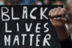 A protester raises a fist next to a Black Lives Matter placard. (Photo credit: LOIC VENANCE/AFP via Getty Images)