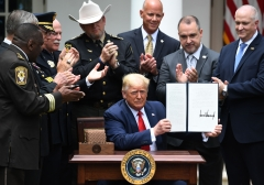 President Donald Trump shows his signature on an Executive Order on Safe Policing for Safe Communities. (Photo credit: SAUL LOEB/AFP via Getty Images)