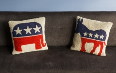 Featured are two pillows on a sofa the Bipartisan Policy Center in Washington DC, one with the Democratic Party symbol of a donkey and the other with the Republican Party Symbol of a elephant. (Photo credit: Brooks Kraft LLC/Corbis via Getty Images)