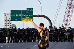 A demonstrator raises her fist in front of a police line blocking freeway access during a protest over the death of George Floyd on May 31 in Minneapolis, Minnesota. - Thousands of National Guard troops patrolled major US cities after five consecutive nights of protests over racism and police brutality that boiled over into arson and looting, sending shock waves through the country. (Photo by CHANDAN KHANNA/AFP via Getty Images)
