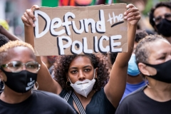 "MANHATTAN, NY - JUNE 19: An African American protester wears a mask and holds a homemade sign that says, ""Defund the Police"" as they perform a peaceful protest walk across the Brooklyn Bridge. (Photo by Ira L. Black/Corbis via Getty Images)"
