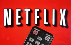 A TV remote is held in front of the Netflix logo. (Photo credit: Chesnot/Getty Images)