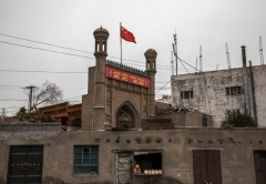 The Chinese flag flies over a mosque shut by authorities in Kashgar, Xinjiang province, in June 2017. (Photo by Kevin Frayer/Getty Images)