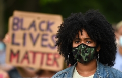 A Black Lives Matter protester is seen in front of a sign. (Photo credit: OLI SCARFF/AFP via Getty Images)