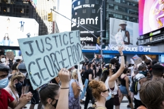 "A protester holds a sign that says, ""Justice for George Floyd"" as the crowd of hundreds pass the New York Police Dept office in Times Square New York in support of black women. (Photo credit: Ira L. Black/Corbis via Getty Images)"