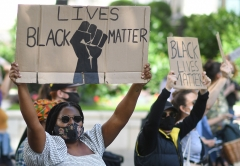 Black Lives Matter protesters display signs. (Photo credit: JUSTIN TALLIS/AFP via Getty Images)