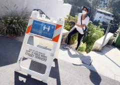 A woman walks past a social distancing sign in Los Angeles, Calif. (Photo credit: David Livingston/Getty Images)