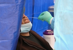 A healthcare worker in New York City takes a nasal swab sample to test for the coronavirus. (Photo by Angela Weiss/AFP via Getty Images)