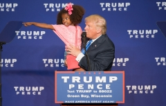 Republican presidential nominee Donald Trump holds a child as he speaks during a rally at the KI Convention Center on October 17, 2016 in Green Bay, Wisc. (Photo credit: TASOS KATOPODIS/AFP via Getty Images)