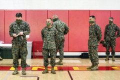 U.S. Marine Corps instructors stand while recruits receive their issued gear at the Marine Corps Recruit Depot (MCRD) on April 13, 2020 in San Diego, California. New COVID-19 distancing practices have gone into effect for new recruits such as standing six feet apart while in formation, a health screening, and a 14-day quarantine period at an off-site hotel before boot camp begins. (Photo by Sandy Huffaker/Getty Images)