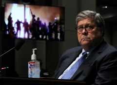 Attorney General William Barr watches a Republican Exhibit video of people rioting, during the House Judiciary Committee hearing in the Congressional Auditorium at the US Capitol Visitors Center July 28, 2020 in Washington, DC. (Photo by CHIP SOMODEVILLA/POOL/AFP via Getty Images)