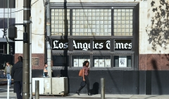 Pedestrians walk past the Los Angeles Times office building. (Photo credit: FREDERIC J. BROWN/AFP via Getty Images)