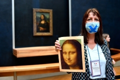 With the Mona Lisa in the background, a Louvre employee prepares to welcome returning visitors this week. (Photo by Aurelien Meunier/Getty Images)