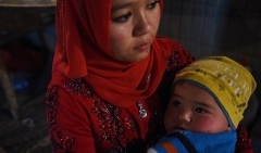 A Uyghur mother and baby at a night market in Xinjiang region. (Photo by Greg Baker/AFP via Getty Images)