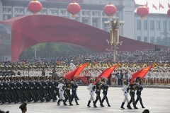 Chinese soldiers march with the national flag, flanked by the flags of the Communist Party of China and the People's Liberation Army during a military parade at Tiananmen Square in Beijing on October 1, 2019. (Photo by GREG BAKER/AFP via Getty Images)