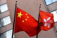 The Chinese and Hong Kong flags fly in Hong Kong on July 30. (Photo by Anthony Wallace/AFP via Getty Images)