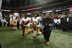 Colin Kaepernick #7 and Eric Reid #35 of the San Francisco 49ers kneel on the sideline, during the anthem, prior to the game against the Atlanta Falcons at the Georgia Dome on December 18, 2016 in Atlanta, Ga. (Photo credit: Michael Zagaris/San Francisco 49ers/Getty Images)