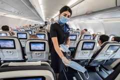 Egyptian cabin crew distribute masks on a flight departing Cairo. Egypt is among 55 countries the State Department continues to advise U.S. citizens not to visit due to the coronavirus pandemic. (Photo by Khaled Desouki/AFP via Getty Images)