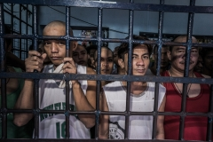 Prisoners stand behind bars. (Photo credit: Giles Clarke/Contributor/Getty Images)