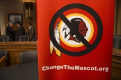 """A poster for the """"Change the Mascot"""" campaign is seen prior to a press conference by the Oneida Indian Nation leaders on Capitol Hill in Washington, D.C., September 16, 2014. (Photo credit: SAUL LOEB/AFP via Getty Images)"""