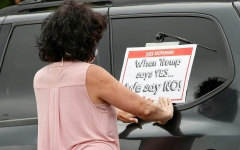 A woman puts a sign on her car prior to the Occupy City Hall Protest and Car Caravan hosted by Chicago Teachers Union in Chicago, Illinois, on Aug. 3, 2020. (Photo credit: KAMIL KRZACZYNSKI/AFP via Getty Images)