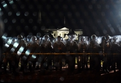 Police officers hold a perimeter behind the metal fence erected in front of the White House to keep protesters out during the sometimes violent protests sparked by the death of George Floyd. (Photo by OLIVIER DOULIERY/AFP via Getty Images)