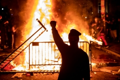 An individual raises a fist near a fire during a riot outside the White House after the death of George Floyd. (Photo credit: SAMUEL CORUM/AFP via Getty Images)