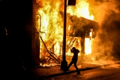 An individual kicks a stone into a burning building set on fire during a demonstration in Minneapolis, Minn., on May 29, 2020, over the death of George Floyd. (Photo credit: CHANDAN KHANNA/AFP via Getty Images)