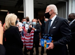 Joe Biden hand over a six pack of local beer, Iron City, as he delivers beer to the Shanksville Volunteer Fire Company in Shanksville, Pa., Sept. 11, 2020. (Photo by Jim Watson/AFP via Getty Images)