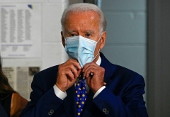 Democraic presidential nominee Joe Biden puts on a mask in Wilmington, Delaware in July. (Photo by Andrew Caballero-Reynolds/AFP via Getty Images)