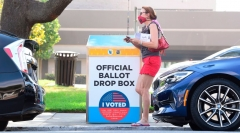 A woman holding her ballot walks past a Vote by Mail Drop Box for the 2020 US Elections on October 5, 2020 in Monterey Park, California, on the first day drop boxes are available to voters. (Photo by FREDERIC J. BROWN/AFP via Getty Images)