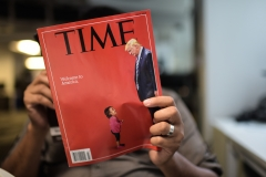 An AFP journalist reads a copy of Time Magazine with a front cover using a combination of pictures showing a crying child taken at the U.S.-Mexico border and a picture of President Donald Trump looking down. (Photo credit: Time Magazine/ERIC BARADAT/AFP via Getty Images)
