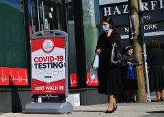 A masked woman walks past a COVID-19 Testing Center in the Borough Park section of Brooklyn on October 9, 2020. More testing means more cases. (Photo by ANGELA WEISS/AFP via Getty Images)