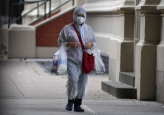 COVID-phobia: A person in a hazmat suit carries groceries on October 5, 2020 in the Brooklyn Borough of New York City. (Photo by ANGELA WEISS/AFP via Getty Images)