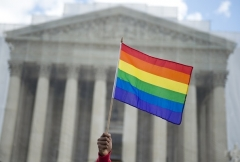 A same-sex marriage supporter waves a rainbow flag in front of the US Supreme Court. (Photo by SAUL LOEB/AFP via Getty Images)