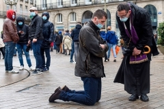 A Catholic priest hears a parishioner's confession outdoors in the city of Nantes on Sunday. (Photo by Sebastien Salom-Gomis/AFP via Getty Images)