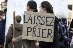 'Let us pray,' reads a sign held by a Catholic worshipper during a rally in Strasbourg on Sunday. (Photo by Frederick Florin/AFP via etty Images)