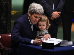 With granddaughter Isabelle Dobbs-Higginson on his lap, Kerry signs the Paris climate agreement at the U.N. in New York on April 22, 2016. (Photo by Timothy A. Clary/AFP via Getty Images)