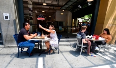 People enjoy outdoor dining Los Angeles, California on July 1, 2020, where new regulations in some counties for certain businesses have come into effect again as coronavirus cases hit record highs.  (Photo by FREDERIC J. BROWN/AFP via Getty Images)