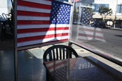 Empty patio tables separated by plastic dividers adorned with American flags are seen at Mel's drive-in diner in West Hollywood, California on November 30, 2020, after Los Angeles County banned outdoor dining. (Photo by ROBYN BECK/AFP via Getty Images)