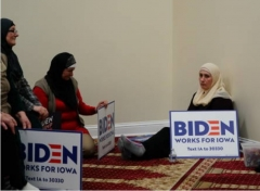 Participants hold Biden campaign sings at the Iowa caucus at the Islamic Education Center Ezan mosque in Des Moines, Iowa, Feb. 3, 2020. (Photo by Elijah Nouvelage/Bloomberg via Getty Images)