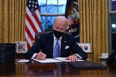 President Joe Biden signs the first of a series of executive orders, in the Oval Office on Wednesday. (Photo by Jim Watson/AFP via Getty Images)