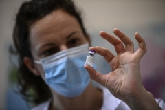 A nurse at the Pasteur Institute in Paris holds a vial of the Pfizer/BioNTech vaccine against COVID-19. (Photo by Christophe Archambault/AFP via Getty Images)