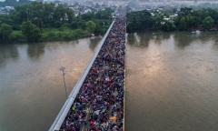 Aerial view of a Honduran migrant caravan heading to the US, on the Guatemala-Mexico international border bridge in Ciudad Hidalgo, Chiapas state, Mexico, on October 20, 2018. - Thousands of migrants who forced their way through Guatemala's northwestern border and flooded onto a bridge leading to Mexico, where riot police battled them back, on Saturday waited at the border in the hope of continuing their journey to the United States. (Photo by PEDRO PARDO/AFP via