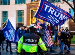 Pro-Trump supporters stand behind police as they argue with counter protesters during a confrontation near Black Lives Matter plaza in Washington, DC on January 5, 2021, on the eve of a rally of supporters of US President Donald Trump to protest the upcoming certification of Joe Biden's Electoral College as president. (Photo by ANDREW CABALLERO-REYNOLDS/AFP via Getty Images)